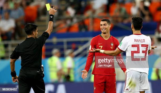 Cristiano Ronaldo of Portugal is shown a yellow card by referee Enrique Caceres during the 2018 FIFA World Cup Russia group B match between Iran and...