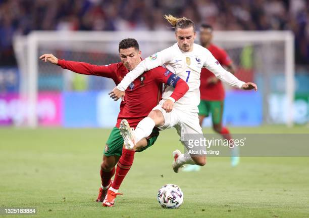 Cristiano Ronaldo of Portugal is tackled by Antoine Griezmann during the UEFA Euro 2020 Championship Group F match between Portugal and France at...