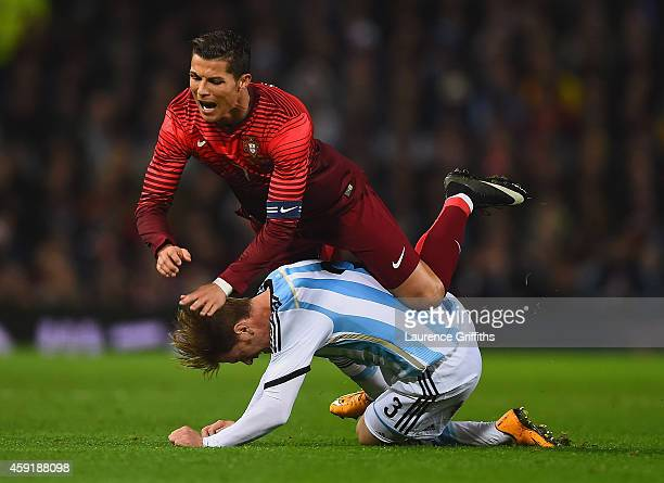Cristiano Ronaldo of Portugal is tackled by Cristian Ansaldi of Argentina during the International Friendly between Argentina and Portugal at Old...
