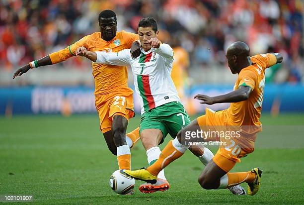 Cristiano Ronaldo of Portugal is tackled by Guy Demel and Emmanuel Eboue of Ivory Coast during the 2010 FIFA World Cup South Africa Group G match...