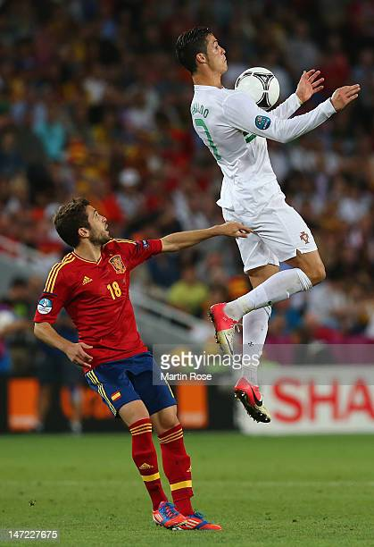 Cristiano Ronaldo of Portugal jumps for a high ball in front of Jordi Alba of Spain during the UEFA EURO 2012 semi final match between Portugal and...