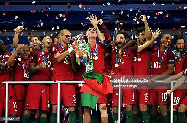 Cristiano Ronaldo of Portugal leads the celebrations as Pepe holds the European Championship trophy after winning 1-0 against France during the UEFA...