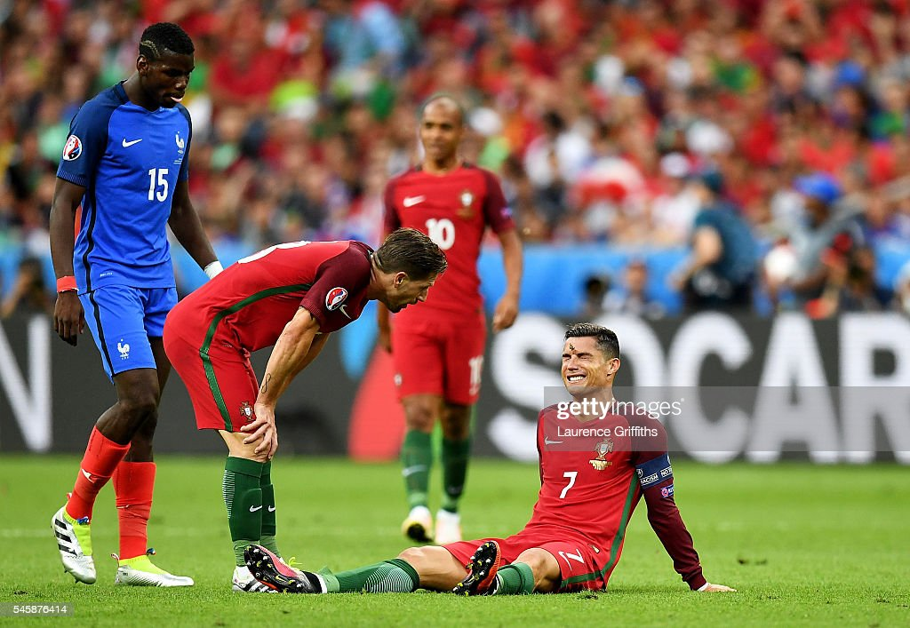 Cristiano Ronaldo of Portugal lies injured as teammate Adrien Silva of Portugal (L) checks on him during the UEFA EURO 2016 Final match between Portugal and France at Stade de France on July 10, 2016 in Paris, France.