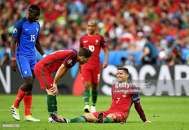 Cristiano Ronaldo of Portugal lies injured as teammate Adrien Silva of Portugal checks on him during the UEFA EURO 2016 Final match between Portugal...
