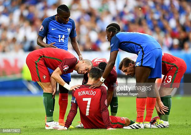 Cristiano Ronaldo of Portugal lies injured as teammate Pepe of Portugal checks on him during the UEFA EURO 2016 Final match between Portugal and...