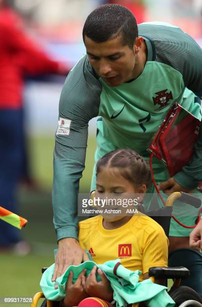 Cristiano Ronaldo of Portugal lines up with a mascot prior to the FIFA Confederations Cup Russia 2017 Group A match between Russia and Portugal at...