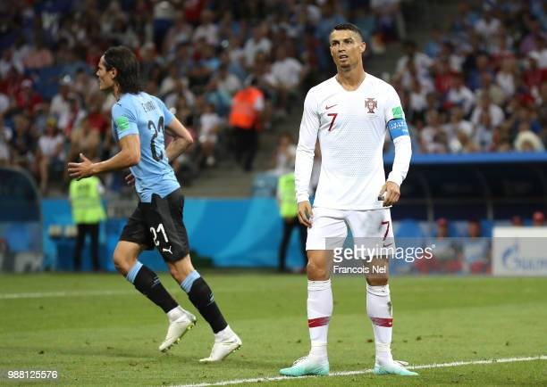 Cristiano Ronaldo of Portugal looks dejected as Edinson Cavani of Uruguay celebrates scoring his side's first goal during the 2018 FIFA World Cup...