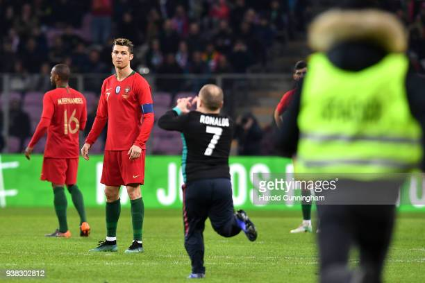 Cristiano Ronaldo of Portugal looks on as a spectator enters the pitch during the International Friendly match between Portugal v Netherlands at...