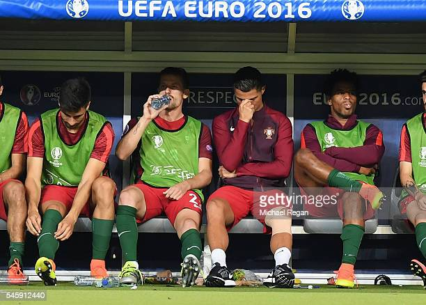 Cristiano Ronaldo of Portugal looks on from the bench during extratime of the UEFA EURO 2016 Final match between Portugal and France at Stade de...