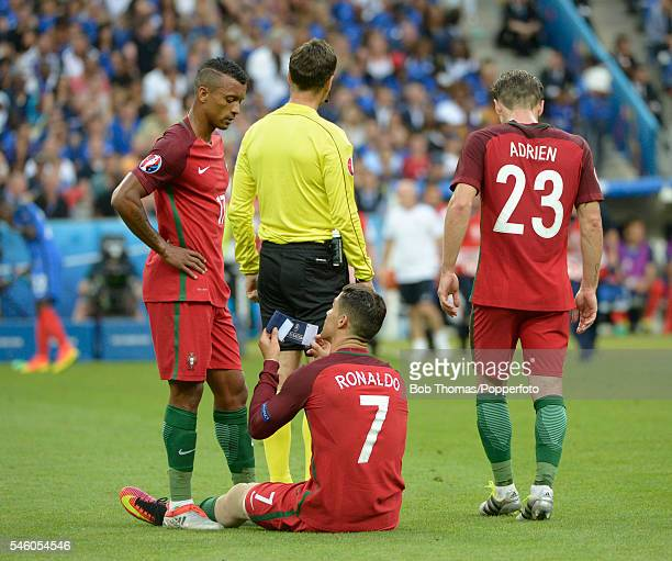 Cristiano Ronaldo of Portugal passes his captains armband to his team mate Nani before being taken off by a stretcher due to an injury during the...