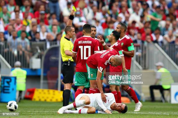 Cristiano Ronaldo of Portugal recoils with an injury on the floor as Referee Mark Geiger shows Mehdi Benatia of Morocco a yellow card behind during...
