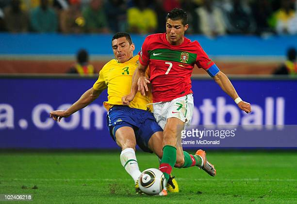 Cristiano Ronaldo of Portugal runs with the ball as Lucio of Brazil challenges during the 2010 FIFA World Cup South Africa Group G match between...