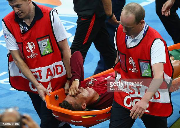 Cristiano Ronaldo of Portugal shows his emotion while being taken off by a stretcher during the UEFA EURO 2016 Final match between Portugal and...