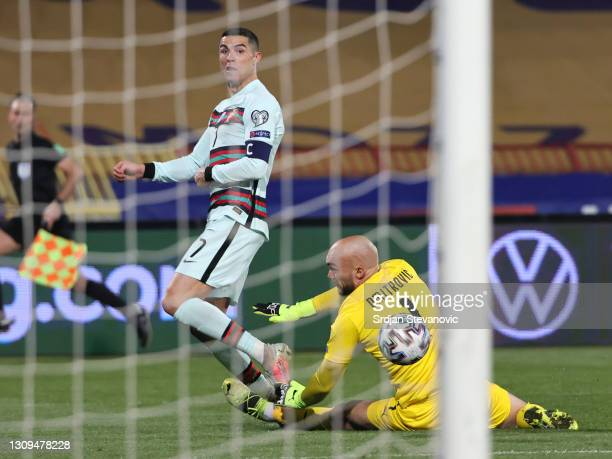 Cristiano Ronaldo of Portugal takes a shot under pressure from Marko Dmitrovic of Serbia during the FIFA World Cup 2022 Qatar qualifying match...