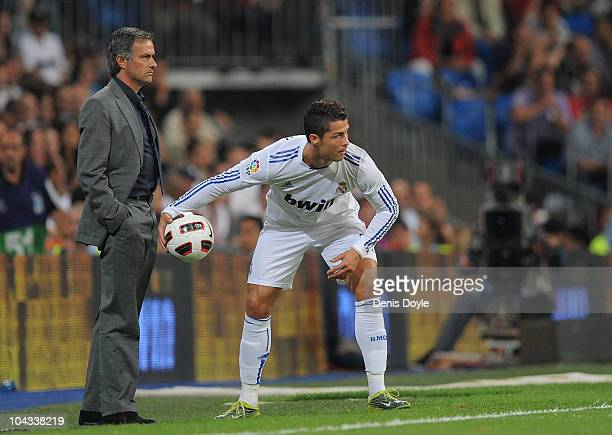 Cristiano Ronaldo of Ral Madrid throws the ball back in play beside Real manager Jose Mourinho during the La Liga match between Real Madrid and...