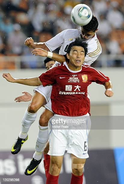 Cristiano Ronaldo of Real Madrid and Feng Xiaoting of Guangzhou Evergrande jumps for the ball during the preseason friendly match between Guangzhou...