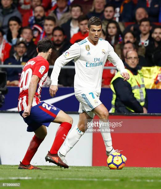 Cristiano Ronaldo of Real Madrid and Juanfran Torres of Atletico de Madrid compete for the ball during the La Liga match between Atletico Madrid and...