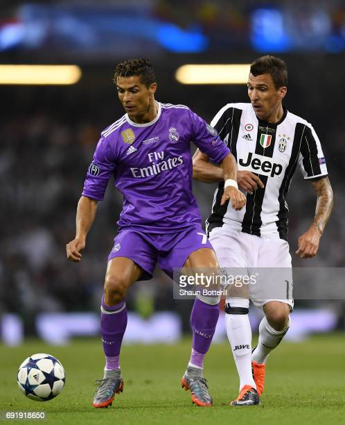 Cristiano Ronaldo of Real Madrid and Mario Mandzukic of Juventus battle for possession during the UEFA Champions League Final between Juventus and...