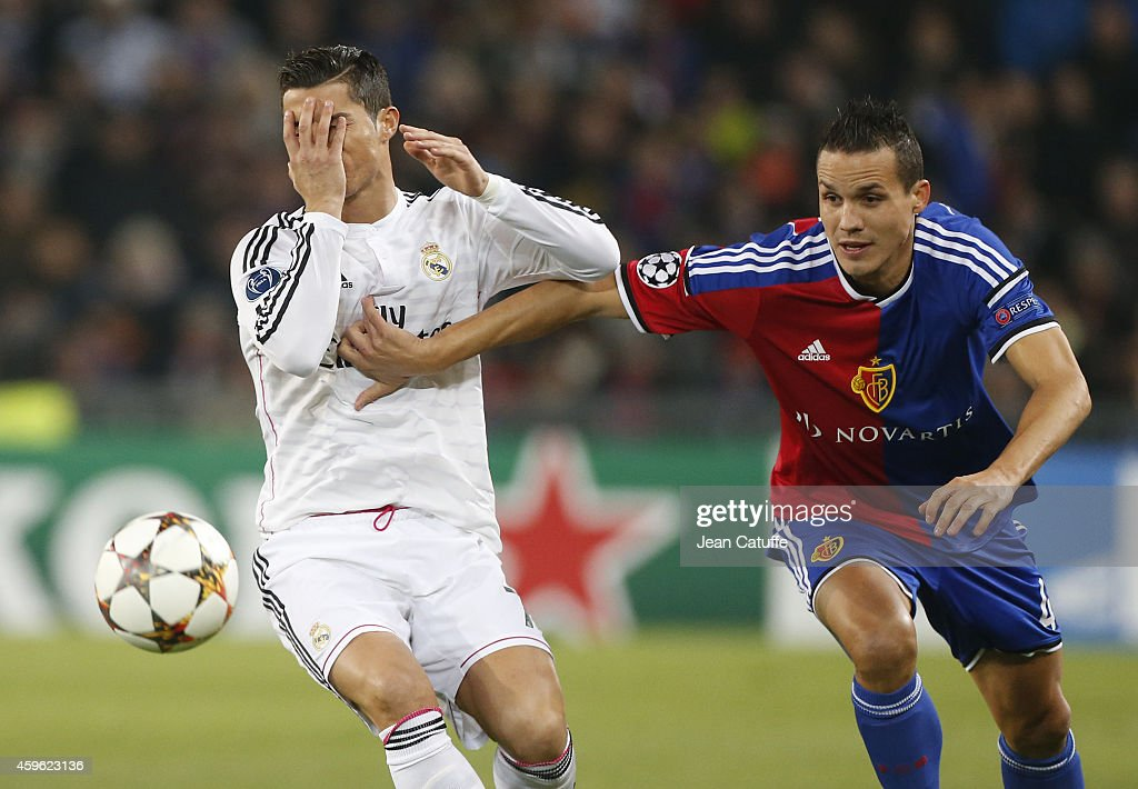 Cristiano Ronaldo of Real Madrid and Philipp Degen of FC Basel in action during the UEFA Champions League Group B match between FC Basel 1893 and Real Madrid CF at St. Jakob-Park stadium on November 26, 2014 in Basel, Basel-Stadt, Switzerland.