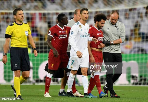 Cristiano Ronaldo of Real Madrid and Sadio Mane of Liverpool console Mohamed Salah of Liverpool as he leaves the pitch injured during the UEFA...