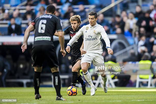 Cristiano Ronaldo of Real Madrid battles for the ball with Sergi Samper Montana of Granada CF during their La Liga match between Real Madrid and...