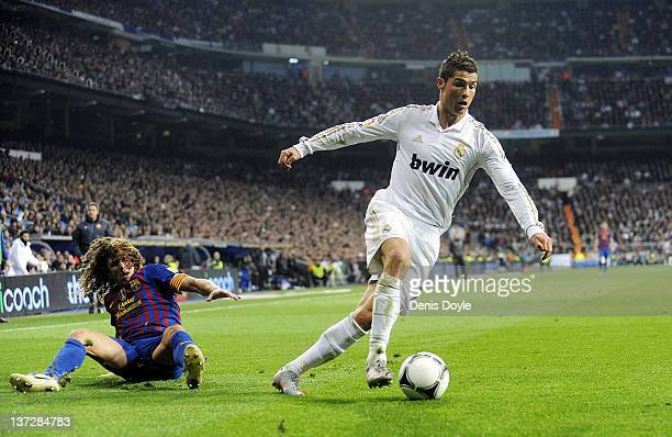 Cristiano Ronaldo of Real Madrid beats Carles Puyol of Barcelona during the Copa del Rey Quarter Finals match between Real Madrid and Barcelona at...
