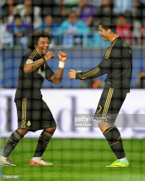 Cristiano Ronaldo of Real Madrid celebrates with Marcelo after scoring his third goal during the La Liga match between Malaga CF and Real Madrid CF...