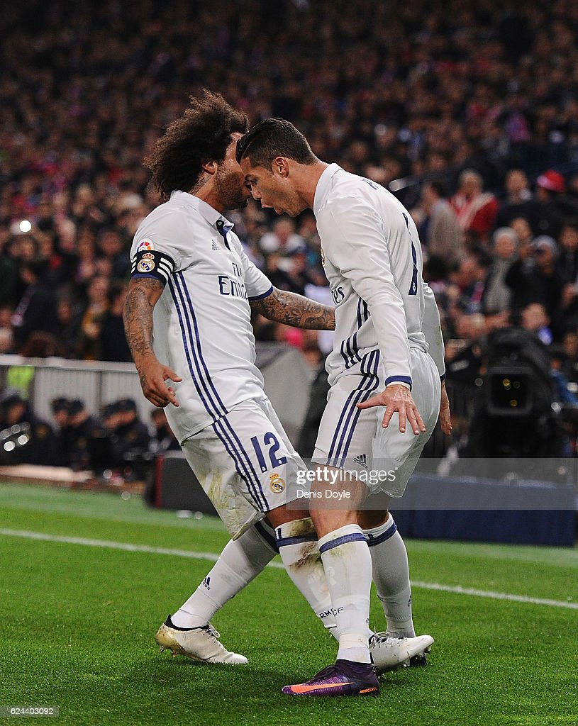 Cristiano Ronaldo of Real Madrid celebrates with Marcelo after scoring Real's first goal during the La Liga match between Club Atletico de Madrid and Real Madrid CF at Vicente Calderon Stadium on November 19, 2016 in Madrid, Spain.