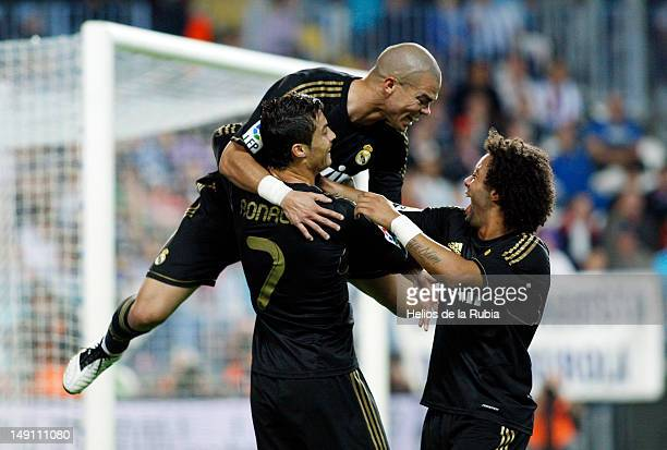 Cristiano Ronaldo of Real Madrid celebrates with Marcelo Vieira and Pepe after scoring his third goal during the La Liga match between Malaga CF and...