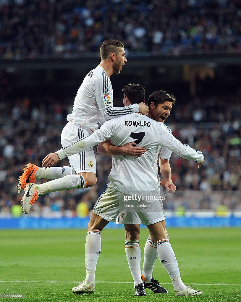 Cristiano Ronaldo of Real Madrid celebrates with Sergio Ramos (L) and Xabi Alonso after scoring Real's opening goal during the La Liga match between Real Madrid CF and Levante UD at Santiago Bernabeu stadium on March 9, 2014 in Madrid, Spain.
