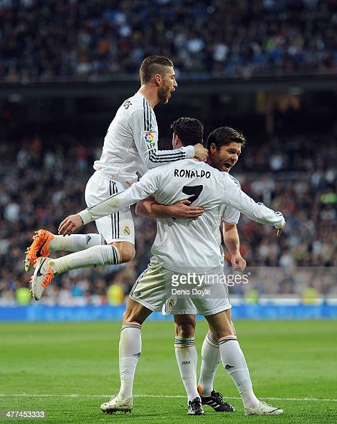 Cristiano Ronaldo of Real Madrid celebrates with Sergio Ramos and Xabi Alonso after scoring Real's opening goal during the La Liga match between Real...