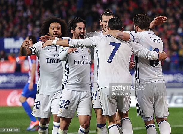 Cristiano Ronaldo of Real Madrid celebrates with teammates after scoring Real's 3rd goal during the La Liga match between Club Atletico de Madrid and...