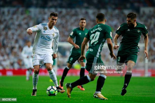 Cristiano Ronaldo of Real Madrid CF competes for the ball with Javi Garcia of Real Betis Balompie and his teammate Ruben Castro during the La Liga...