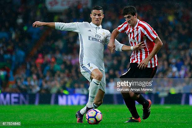 Cristiano Ronaldo of Real Madrid CF competes for the ball with Mikel San Jose of Athletic Club during the La Liga match between Real Madrid CF and...