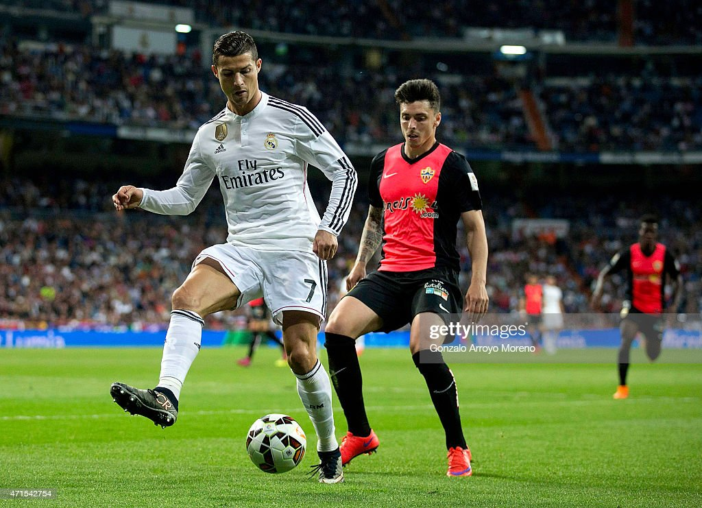 Cristiano Ronaldo (L) of Real Madrid CF competes for the ball with Joaquin Navarro JImenez (R) of Almeria UD during the La Liga match between Real Madrid CF and UD Almeria at Estadio Santiago Bernabeu on April 29, 2015 in Madrid, Spain.