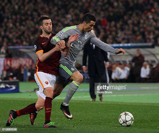 Cristiano Ronaldo of Real Madrid CF competes for the ball with Miralem Pjanic of AS Roma during the UEFA Champions League round of 16 first leg match...