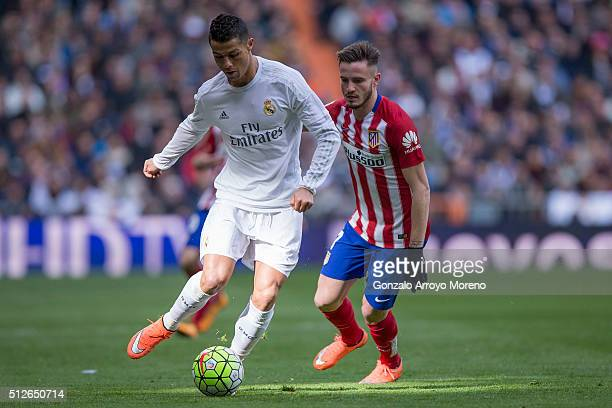 Cristiano Ronaldo of Real Madrid CF competes for the ball with Saul Niguez of Atletico de Madrid during the La Liga match between Real Madrid CF and...