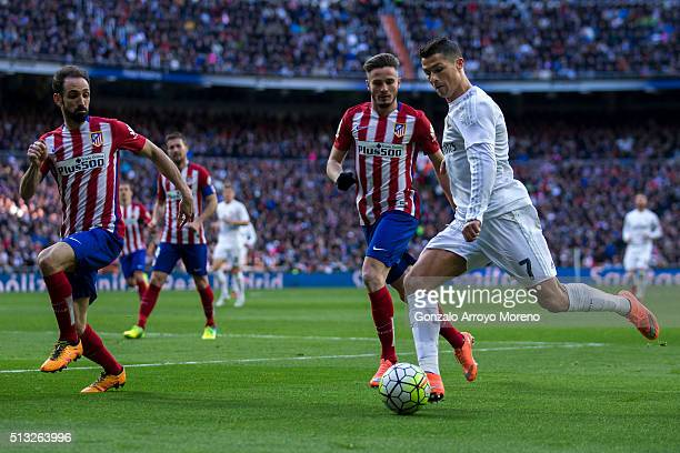 Cristiano Ronaldo of Real Madrid CF competes for the ball with Saul Niguez and his teammate Juan Francisco Torres alias Juanfran of Atletico de...
