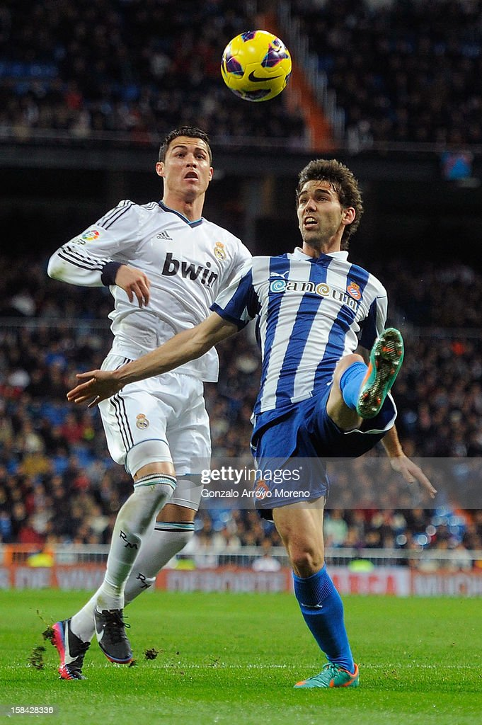 Cristiano Ronaldo (L) of Real Madrid CF competes for the ball with Victor Alvarez RCD Espanyol during the La Liga match between Real Madrid CF and RCD Espanyol at Estadio Santiago Bernabeu on December 16, 2012 in Madrid, Spain.