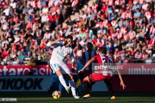 Cristiano Ronaldo of Real Madrid CF dribbles Marc Muniesa of Girona FC during the La Liga match between Girona and Real Madrid at Estadi de Montilivi...