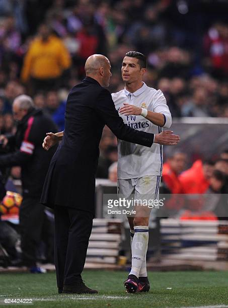 Cristiano Ronaldo of Real Madrid CF embraces Real manager Zinedine Zidane on being substituted in the La Liga match between Club Atletico de Madrid...