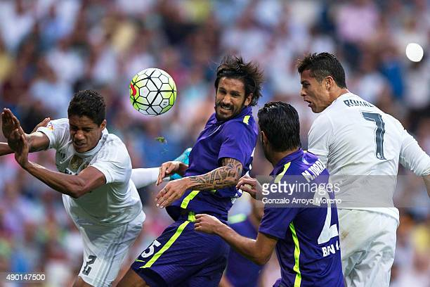 Cristiano Ronaldo of Real Madrid CF heads the ball behind Miguel Torres and Marcos Angeleri both of Malaga CF and his teammate of Real madrid Raphael...
