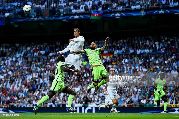 Cristiano Ronaldo of Real Madrid CF heads the ball towards goal under a challenge by Nicolas Otamendi of Manchester City FC during the UEFA Champions...