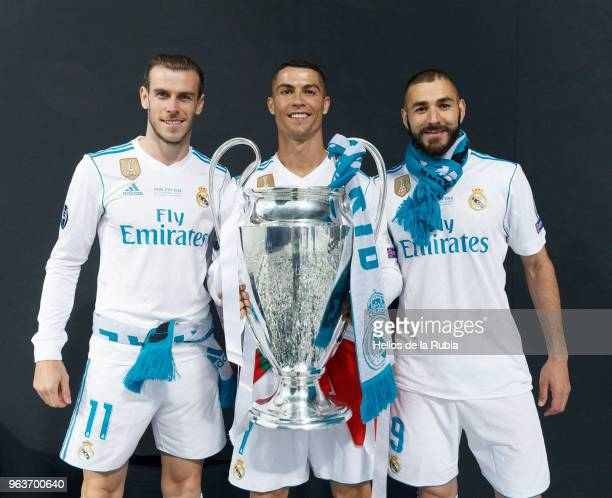 Cristiano Ronaldo of Real Madrid CF holds the trophy as he poses for a picture with his teammates Karim Benzema and Gareth Bale during the...