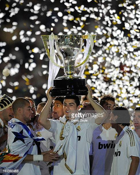 Cristiano Ronaldo of Real Madrid CF holds up the La Liga trophy as he celebrates with team-mates after the La Liga match between Real Madrid CF and...