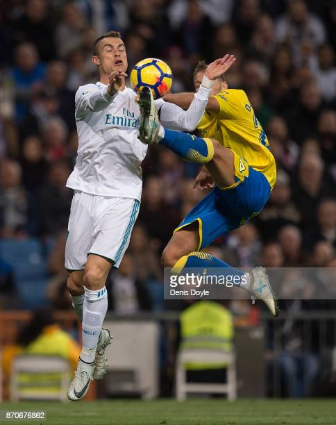 Cristiano Ronaldo of Real Madrid CF is challenged by David Simon of Las Palmas during the La Liga match between Real Madrid and Las Palmas at Estadio...