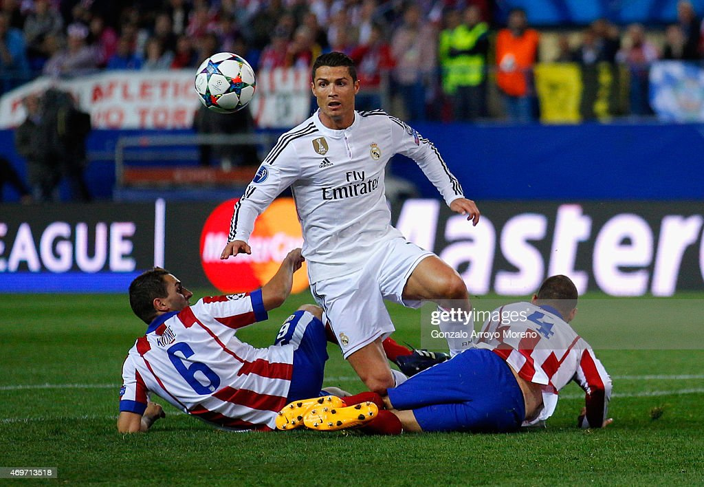 Cristiano Ronaldo of Real Madrid CF is tackled by Koke of Atletico Madrid and Mario Suarez of Atletico Madrid during the UEFA Champions League Quarter Final First Leg match between Club Atletico de Madrid and Real Madrid CF at Vicente Calderon Stadium on April 14, 2015 in Madrid, Spain.
