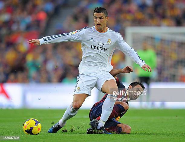 Cristiano Ronaldo of Real Madrid CF is tackled by Xavi Hernandez of FC Barcelona during the La Liga match between FC Barcelona and Real Madrid CF at...