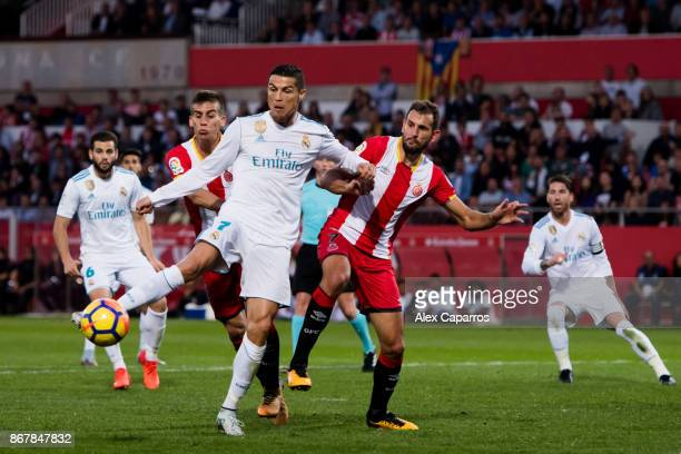 Cristiano Ronaldo of Real Madrid CF kicks the ball under pressure from Christian Stuani of Girona FC during the La Liga match between Girona and Real...