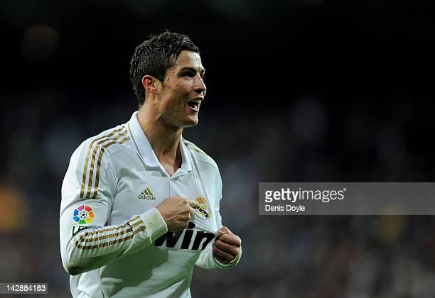 Cristiano Ronaldo of Real Madrid CF points to the club's crest on his shirt as he celebrates after scoring his team's second goal during the La Liga...